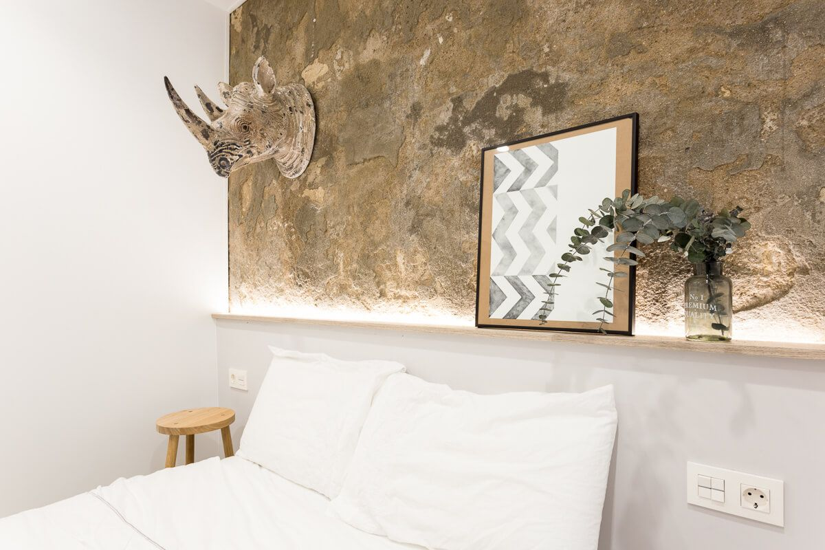Pared piedra vista de reforma de apartamento en Alicante por Araque Maqueda